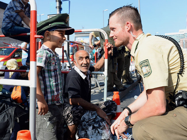 Bavarian soldier makes a young Syrian refugee boy smile as he enters Munich
