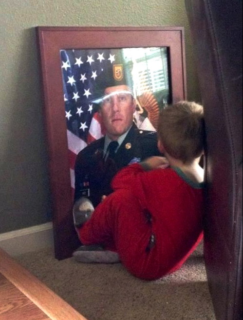 Little boy looking at his veteran father