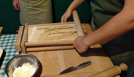 Making spaghetti on the pasta chitarra guitar at Cook Eat Italian cooking class in Florence