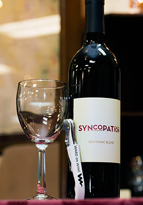 2015 Syncopation Rhythmic Red blend with a glass and Sommelier knife